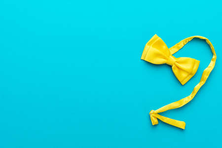 Top view  of yellow silk bow tie over turquoise blue Zdjęcie Seryjne