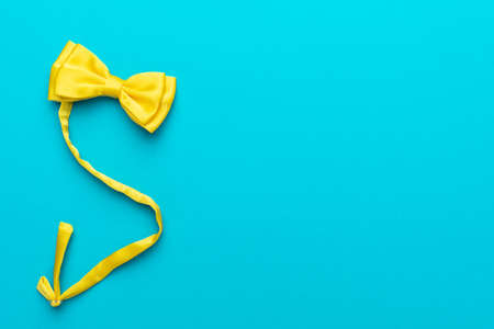 Top view  of yellow satin bow tie over turquoise blue