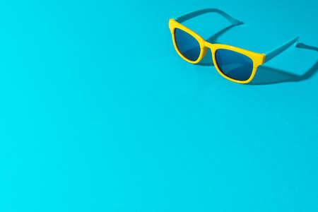 Yellow sunglasses with harsh shadow as summer concept. Zdjęcie Seryjne