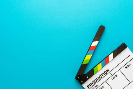 Top view of open white acrylic clapperboard over turquoise blue