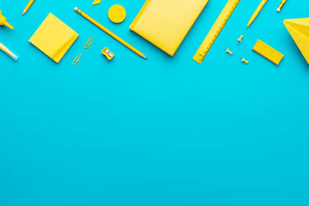 Top view  of yellow school stationery on turquoise blue  with copy space.
