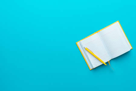 Top view  of opened notebook and yellow pen over it on turquoise blue  with copy space.