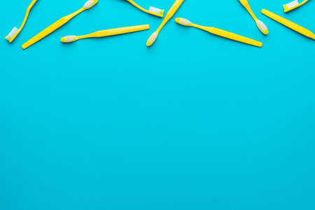 Top view  of many new yellow toothbrushes over turquoise blue  with copy space.