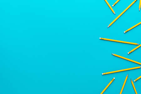 Top view  of yellow sharpened pencils over turquoise blue  with copy space.
