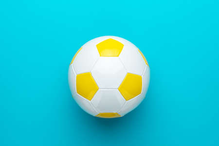 Top view  of white and yellow soccer ball over turquoise blue  with copy space. Stock Photo