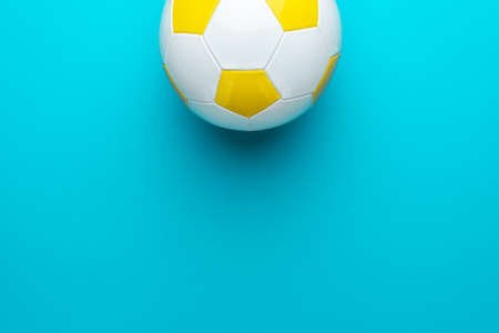 Top view of part of white and yellow soccer ball over turquoise blue  with copy space. Zdjęcie Seryjne