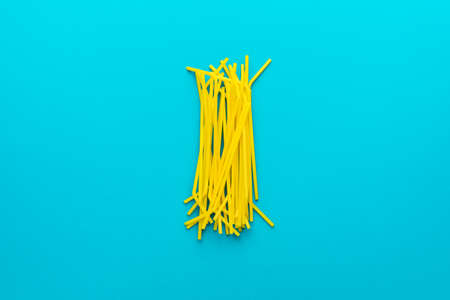 Top view  of pile of yellow drinking straws over turquoise blue  with copy space.