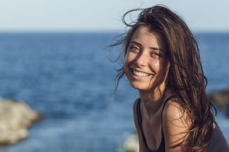 Close-up portrait of cheerful suntanned young woman looking into camera over sea and blue sky  with copy space.