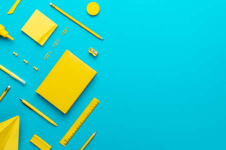 Top view  of yellow stationery over turquoise blue  with copy space. Zdjęcie Seryjne