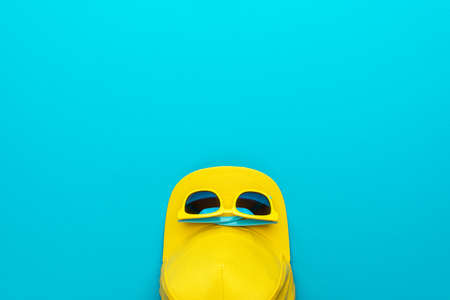 Flat lay image of summertime accessories over turquoise blue background with copy space. Top view photo of yellow baseball cap and sunglasses as summer concept.