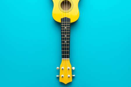 Yellow colored ukulele on the turquoise blue background. MInimalist photo of ukulele guitar with copy space.