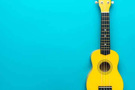 Overhead photo of ukulele with copy space. Yellow colored wooden ukulele guitar on the turquoise blue background. Standard-Bild