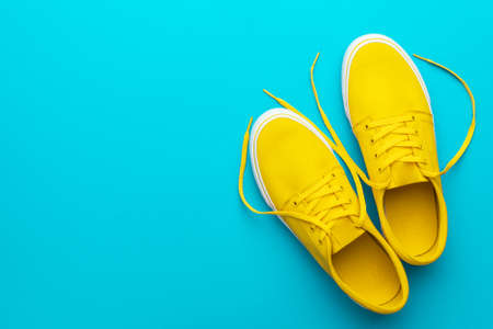 Minimalist flat lay image of yellow summer footwear over blue turquoise background with copy space. Top view photo of pair of yellow untied sneakers.