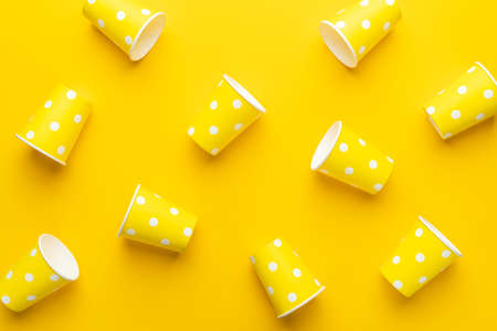Disposable paper cups on the yellow background. Top view of yellow cups on the table. Minimalist photo of used paper cups as end of the party concept.