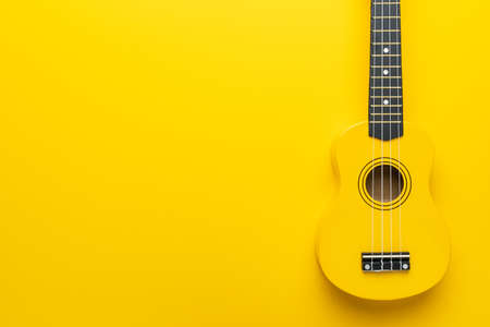 Overhead photo of ukulele with copy space. Yellow colored wooden ukulele guitar on the yellow background.