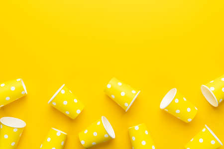 End of the party concept with copy space. Disposable paper cups on yellow background. Top view of used yellow cups on the table.