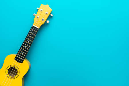 Top view of ukulele with copy space. Yellow colored wooden ukulele guitar on the turquoise blue background.