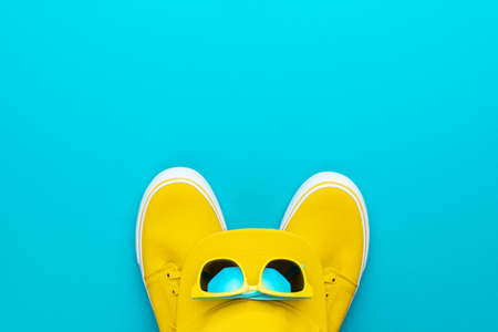 Top view photo of yellow baseball cap, sunglasses and sneakers as summer concept. Flat lay image of summertime teenage accessories over turquoise blue background with copy space.
