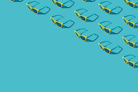 Top view of many vivid color plastic sunglasses on turquoise blue background with copy space. Minimalist photo pattern of stylish yellow sunglasses with harsh shadow as summer concept.
