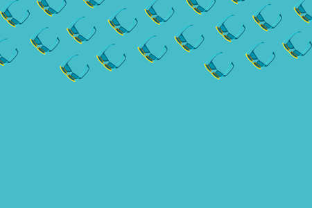 Overhead composition of many vivid color plastic sunglasses on turquoise blue background with copy space. Minimalist photo pattern of stylish yellow sunglasses with harsh shadow as summer concept. Standard-Bild