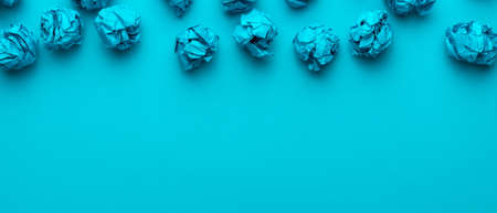 Top view of blue crumpled paper balls over turquoise blue background with copy space and upside composition. Brainstorming concept with blue crumpled office paper. Standard-Bild