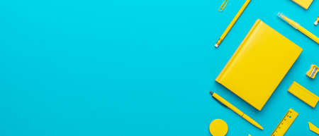 Top view photo of yellow stationery over turquoise blue background with copy space. Flat lay image of stickers, pencils, notebook, ball-point pen, eraser, sharpener, paerclips, pushpins and ruler.