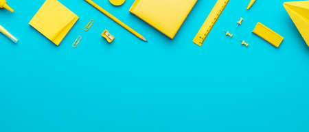 Top view photo of yellow school stationery on turquoise blue background with copy space. Flat lay image of different stationery in order as back to school concept