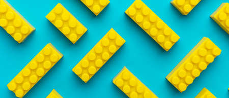 Top view of plastic blocks background. Flat lay image of toy background made with yellow building blocks from child constructor. Bright yellow plastic building blocks on turquoise blue background.