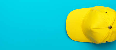 Top view of the yellow baseball cap over the blue turquoise background. Minimalist flat lay photo of the bright yellow cap with copy space