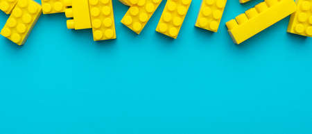 Top view of yellow plastic blocks. Flat lay image of yellow blocks from child constructor. Bright plastic blocks on turquoise blue background with copy space.