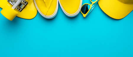 Top view of yellow modern teenage accessories. Flat lay image of yellow baseball cap, sunglasses, sneakers, plastic mini cruiser skateboard over blue turquoise background with copy space Standard-Bild