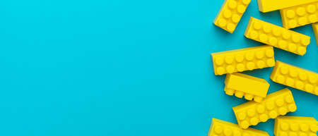 Top view of yellow plastic blocks. Right side composition of yellow building blocks from child constructor. Bright plastic blocks on turquoise blue background with copy space. Standard-Bild
