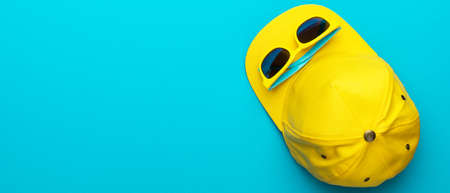 Top view photo of yellow baseball cap and sunglasses as summer concept. Flat lay image of summertime accessories over turquoise blue background with copy space and left side position. Standard-Bild