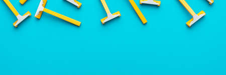 Many disposable unisex razors on the turquoise blue background. Top view of yellow plastic razors with copy space Standard-Bild