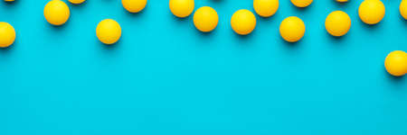 many balls for table tennis on turquoise blue background. flat lay image of many yellow table tennis balls with copy space. minimalist photo of yellow equipment