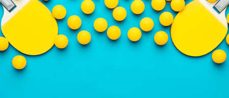two rackets and many balls for table tennis on turquoise blue background. flat lay image of many table tennis balls and paddles. minimalist photo of yellow equipment with copy space