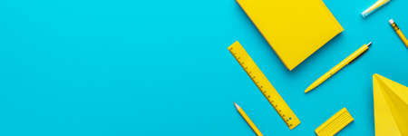 Top view photo of yellow stationery over turquoise blue background with copy space. Flat lay image of different stationary objects as back to school background.