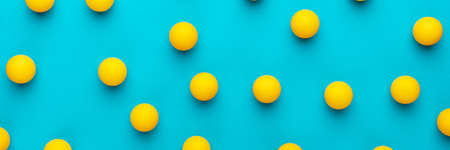 Flat lay image of many yellow balls. Many balls for table tennis on turquoise blue background.