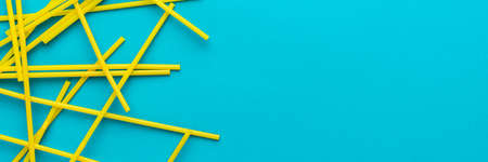 Flat lay photo of many yellow bendy cocktail straws. Top view of cocktail straws on turquoise blue background with copy space.