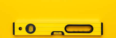 Yellow spirit level on the yellow background. Panoramic photo of bubble level with some copy space. Standard-Bild