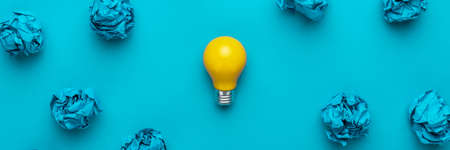 New idea concept with crumpled office paper and light bulb. Top view of great business idea concept over blue background. Creative solution during brainstorming session concept.