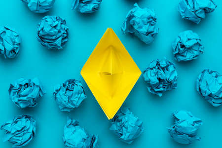 New idea concept with crumpled office paper and yellow paper ship. Top view of great business idea concept over blue background with yellow paper boat in the center. Reklamní fotografie