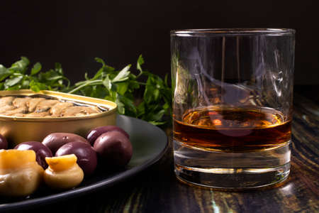 A glass of whiskey and an elite appetizer on a black background. Olives, pickled mushrooms, champignons, sprats and an expensive alcoholic drink.