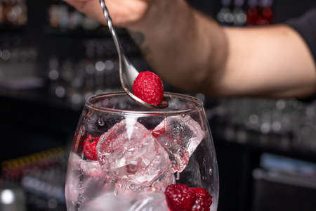 Ice cubes and raspberries in a glass. The process of nailing the cocktail. Stock Photo