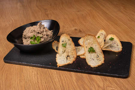 Pate of beef liver and meat with herbs in a black plate with crunchy toast. Restaurant food.