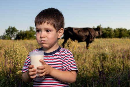 A small child boy 3 years old for the first time tastes cows milk, does not like milk, crooked, writhes the face.