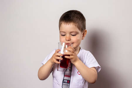 A little boy in a white T-shirt holds a glass of cherry juice. Vitamins for children.