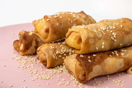 Pancakes homemade with sesame seeds on a pink plate. Delicious sweet breakfast with sugar.