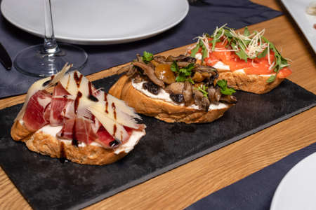 Three delicious juicy bruschettas of loaf with mushrooms, bacon, cheese and tomatoes on a black marble stand. Snacks with bread in the restaurant. Zdjęcie Seryjne