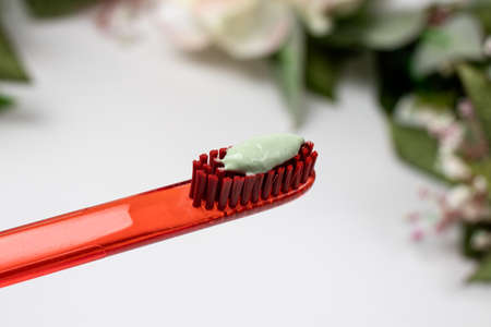 Red toothbrush with green natural toothpaste on a white background.